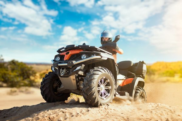 Summer offroad adventure on atv in sand quarry. Male rider in helmet on quad bike in sandpit