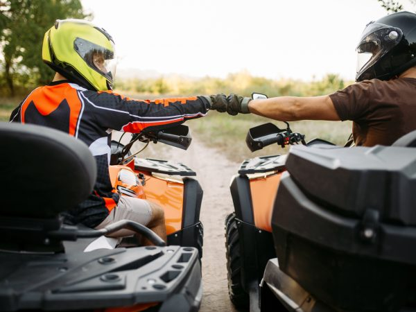 Two atv riders in helmets hits fists for good luck before extreme offroad riding, back view. Freeriding on quad bike, quadbike summer adventure